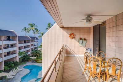 Pink tiled lanai with patio table overlooking swimming pool