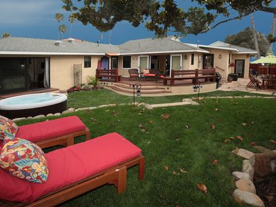 Backyard w/ lounges, outdoor shower, dining area, spa