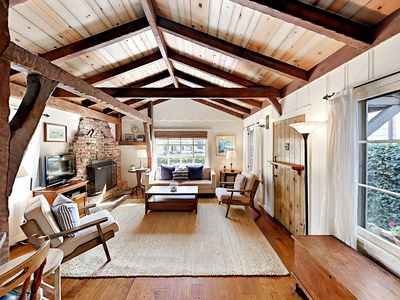 Living Area - Cozy living area with vaulted ceilings, wood beams, and original stone fireplace.