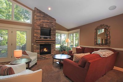 First floor great room with fireplace, vaulted ceiling and sky lights.