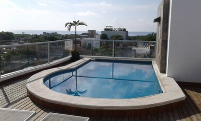 Photo for Ocean view condo with rooftop pool near the beach