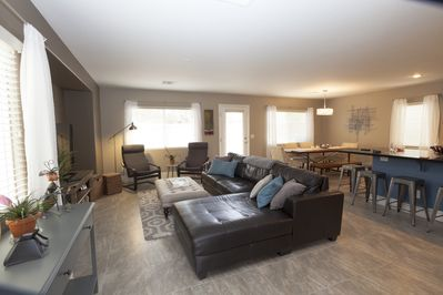 Great room with flat screen TV, dining room, kitchen, door to private yard