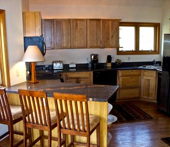 Large kitchen with newer appliances, and many supplies.