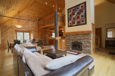 Great room with living and dining spaces and library loft above.