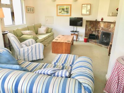House sitting room with 2 sofas, armchair, open fire and smart TV