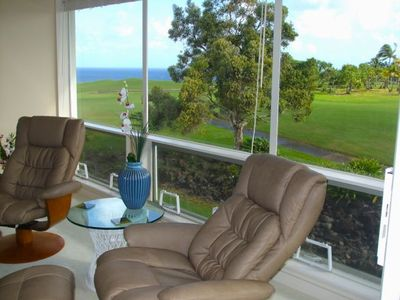 View of golf course and ocean from living room. Swivel chairs face view or room.