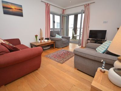 Lounge area with sea views and French doors leading to enclosed balcony
