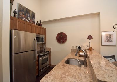 The fully equipped kitchen has granite counters and stainless appliances.