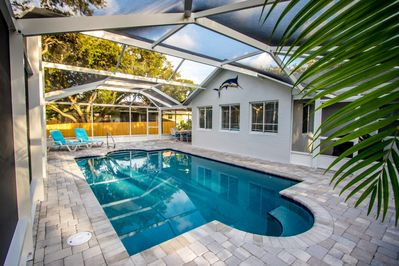 Outdoor living with screened heated pool and adjacent BBQ porch
