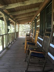 Front porch with 5 rocking chairs with cushions.