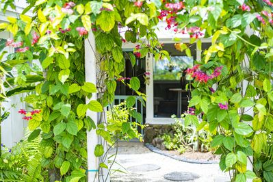 Private entry through Balinese archway with flowering vines