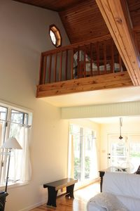 View of wood ceilings, large windows and cozy loft upstairs.