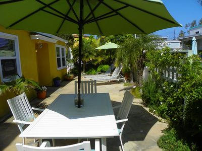 Large, sunny flagstone patio with dining and lounges & umbrellas.