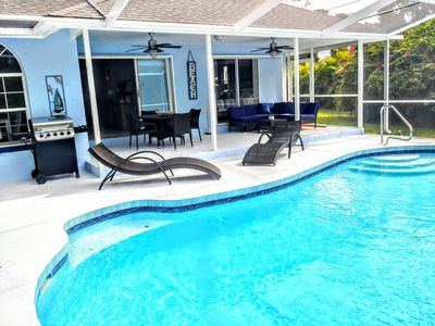 Outdoor heated pool and lanai with dining and lounging area