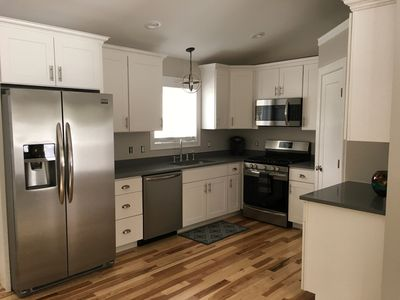 New Kitchen with white cabinets, gray quartz countertops, Hickory flooring