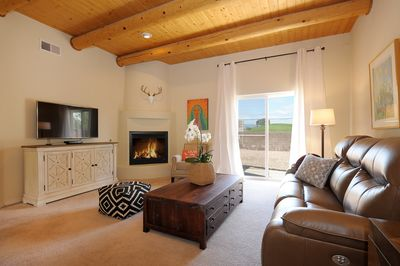 Living room with fireplace, big screen TV, reclining sofa  and golf course view.