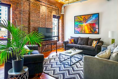 Cozy living room with tons of seating, brick walls, high ceilings and more