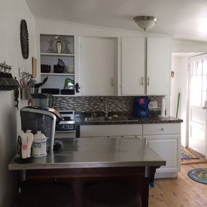 Large, well equipped kitchen has a center island with seating, full size fridge.