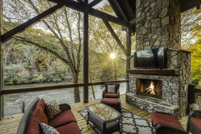 Covered Deck with fireplace over looking Toccoa River