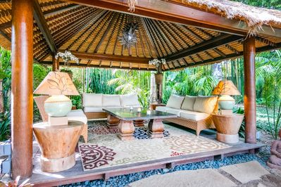 Outdoor Living Room - Get cozy in the outdoor living room, sheltered under a thatched-roof cabana.