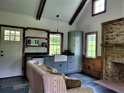 Great Room with stone fireplace, vaulted ceiling, and kitchenette.