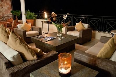 nighttime on the veranda with comfy seating and an additional dining area