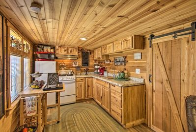 The cozy studio features a rustic interior with wooden walls and floors.