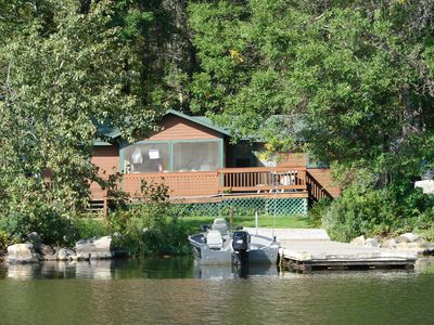 The cabin sits at the waters edge with a dock right outside the door.
