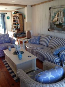 queen pullout sofa and two very comfy chairs with large hassock and coffee table with wicker storage baskets