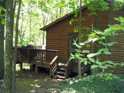 The furnished deck on the side/back of the house look at a lovely wooded area.