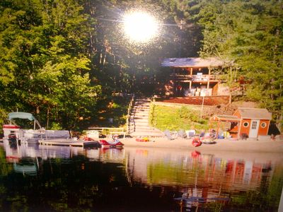 View of beach, boat dock, tiki hut and cabin from the lake