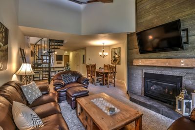 Open concept living/dining area with flat screen TV and fireplace
