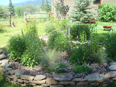Raised stone gardens filled with bright colored flowers and grasses