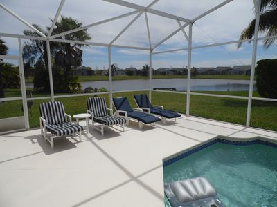 Pool area with lake view. There are 4 loungers along with table and 4 chairs.