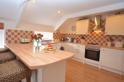 Open plan well equipped kitchen with breakfast bar.