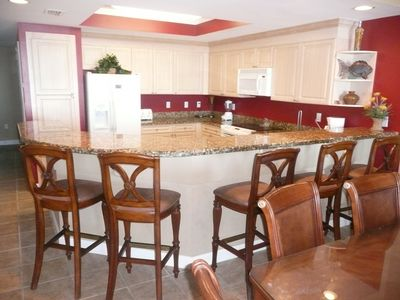 Kitchen with granite  counter tops and 6 bar stools