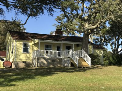 A Cottage with a View has a grassy yard amidst shady live oaks.