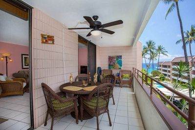 Pink tiled lanai with wicker patio table and chairs overlooking pool & ocean