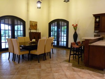 Formal dining and bar stool seating. French doors to covered patio.
