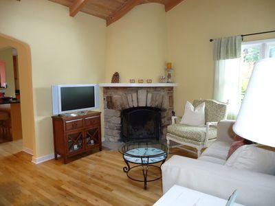 Living room with hardwood floors, lots of light and wood burning fireplace