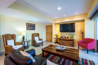 Living room has comfortable seating and a 50 inch TV with cable