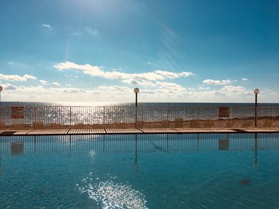 View of the pool and Atlantic Ocean beach with comfortable lounge chairs.