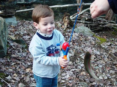 My son with his first trout from the creek in front of the cabin.