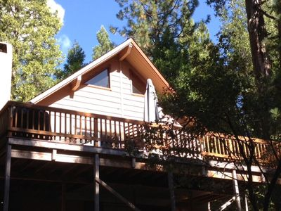 The deck and peak of the roof surrounded by beautiful trees.