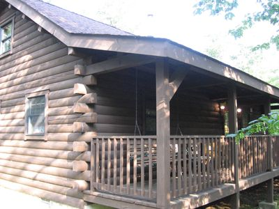 Our cozy log cabin with covered deck and porch swing
