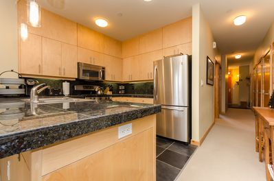 Spacious kitchen has ample counter space, pendant lighting, icemaker, and more!