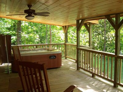 The covered porch features rockers and a hot tub.