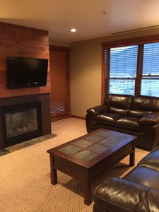 Living room with gas fireplace and large flat-screen TV.