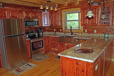 Custom kitchen with stainless appliances, copper sink and granite countertops.