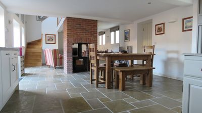 Open plan kitchen, dining and living with central wood burning stove